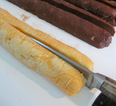 cutting-rolls-of-orange-chocolate-cookie-dough-in-halves-and-quarters-with-floured-knife